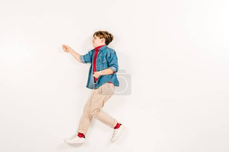 Photo for Top view of adorable kid gesturing while lying on white - Royalty Free Image