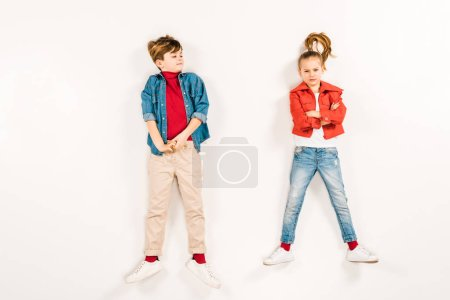 Photo for Top view of kid looking at friend with crossed arms lying on white - Royalty Free Image