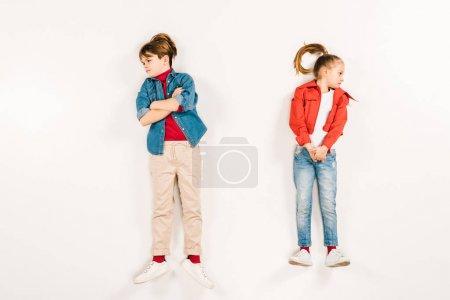 Photo pour Vue supérieure de l'enfant mécontent avec les bras croisés près de l'ami sur le blanc - image libre de droit