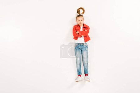 Photo for Top view of displeased kid with crossed arms on white - Royalty Free Image