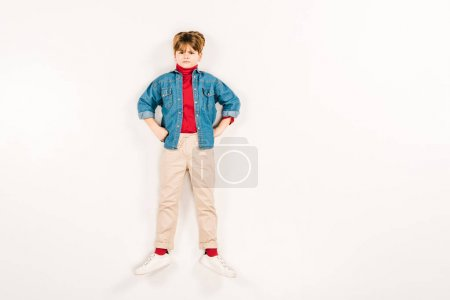Photo for Top view of upset kid with hands on hips lying on white - Royalty Free Image