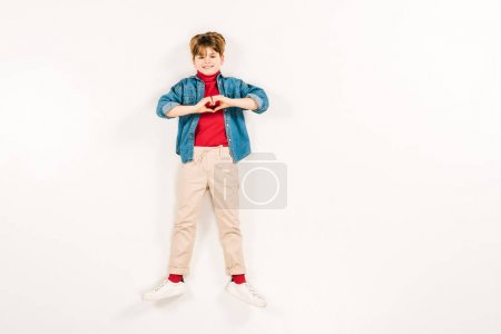 Photo for Top view of cheerful child showing heart-shape sign on white - Royalty Free Image