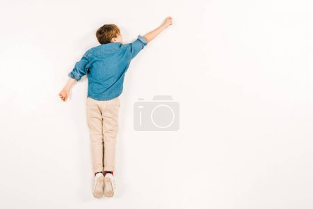 Photo for Top view of kid lying and gesturing on white - Royalty Free Image
