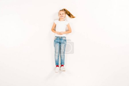 Photo for Top view of happy kid with clenched hands lying on white - Royalty Free Image