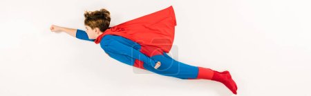 panoramic shot of adorable kid in super hero costume flying on white