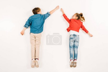 Photo for Top view of cute kids gesturing while lying on white - Royalty Free Image