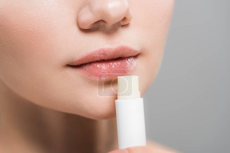 Photo pour Vue recadrée de jeune femme retenant le baume de lèvre d'isolement sur le gris - image libre de droit