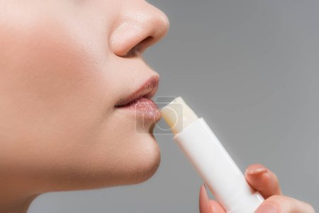 Photo for Cropped view of woman holding lip balm isolated on grey - Royalty Free Image