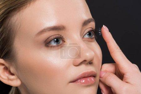 Foto de Hermosa mujer joven que une la lente de contacto aislada en negro - Imagen libre de derechos
