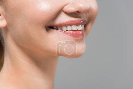 Photo pour Vue recadrée de femme gaie souriant d'isolement sur le gris - image libre de droit