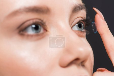 selective focus of woman attaching contact lens isolated on black