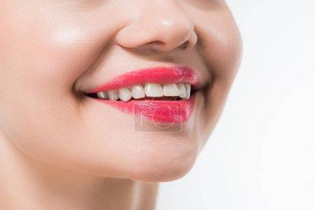 Photo pour Vue recadrée de jeune femme avec des lèvres roses souriant d'isolement sur le blanc - image libre de droit