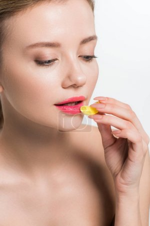 Photo for Attractive nude woman holding yellow jelly candy isolated on white - Royalty Free Image