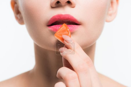 Photo for Cropped view of young woman holding orange jelly candy near lips isolated on white - Royalty Free Image