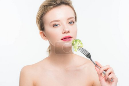 Photo for Attractive naked woman holding silver fork with broccoli near pink lips isolated on white - Royalty Free Image
