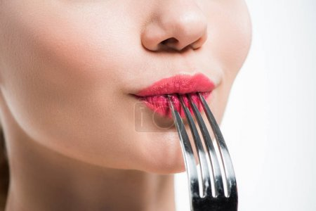 Photo for Cropped view of woman holding silver fork near pink lips isolated on white - Royalty Free Image