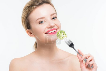 Photo for Happy naked woman holding fork with green ripe broccoli isolated on white - Royalty Free Image