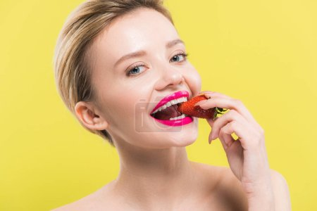 Photo for Attractive woman with pink lips eating strawberry isolated on yellow - Royalty Free Image
