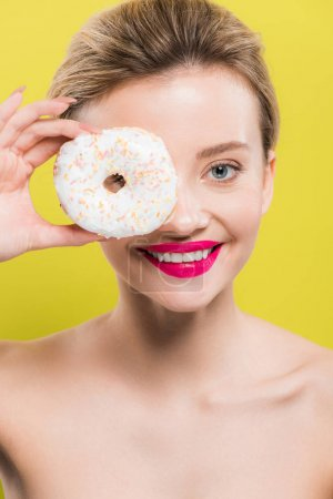 Photo for Cheerful woman covering eye with tasty doughnut isolated on yellow - Royalty Free Image