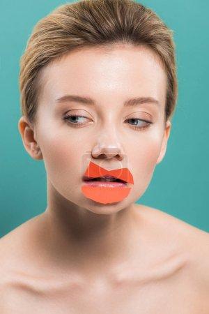 Photo pour Femme nue attirante avec le papier orange sur des lèvres d'isolement sur le bleu - image libre de droit