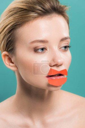 Photo pour Belle jeune femme nue avec le papier orange sur des lèvres d'isolement sur le bleu - image libre de droit
