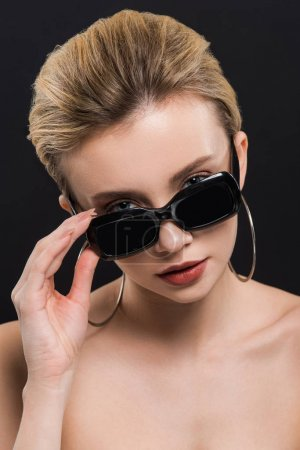 Photo pour Jeune femme attirante touchant des lunettes de soleil d'isolement sur le noir - image libre de droit