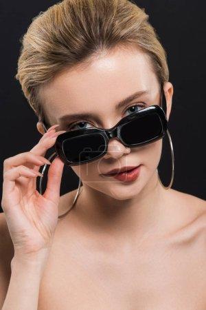 Photo pour Jeune femme attirante mordant des lèvres tout en touchant des lunettes de soleil d'isolement sur le noir - image libre de droit