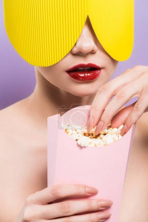 Photo for Young woman holding bucket with salty popcorn isolated on purple - Royalty Free Image