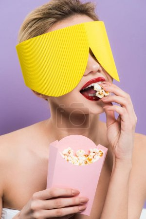 Photo for Young woman holding bucket and eating tasty popcorn isolated on purple - Royalty Free Image