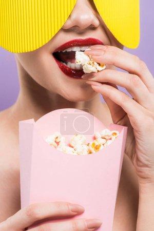 Photo pour Vue recadrée de jeune femme retenant le seau et mangeant le maïs soufflé savoureux d'isolement sur le pourpre - image libre de droit