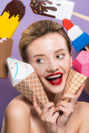 Photo pour Jeune femme nu gai retenant les cônes décoratifs de crème glacée d'isolement sur le pourpre - image libre de droit