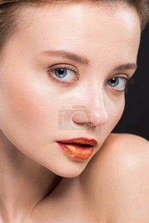 Foto de Close up of beautiful young woman with orange lips isolated on black - Imagen libre de derechos