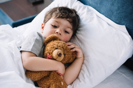 Photo for Cute kid lying in bed with teddy bear at home - Royalty Free Image