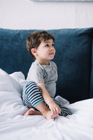 Photo for Cute kid sitting on bed with white bedding at home - Royalty Free Image