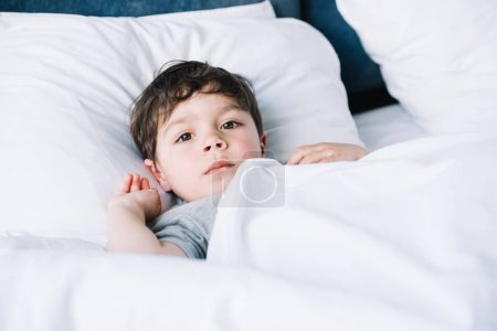 Photo for Cute kid lying on white pillow in bed and looking at camera - Royalty Free Image