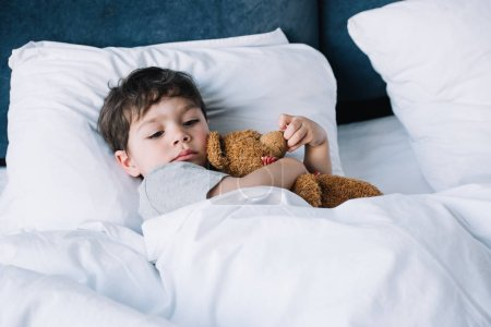 Photo for Cute kid lying on white pillow in bed and holding teddy bear - Royalty Free Image
