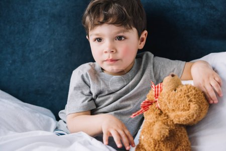 Photo for Cute child sitting near teddy bear in bedroom at home - Royalty Free Image