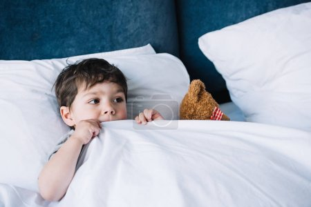 Photo for Kid lying on white pillow in bed near teddy bear at home - Royalty Free Image