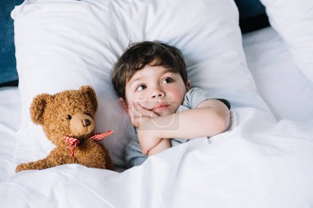 Photo for Adorable kid lying on white pillow near teddy bear at home - Royalty Free Image