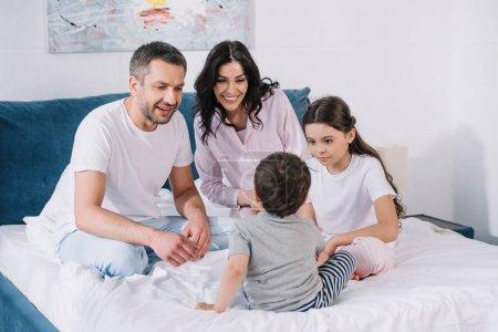 Photo pour Parents heureux s'asseyant sur le lit près de la fille et regardant le fils d'enfant en bas âge - image libre de droit