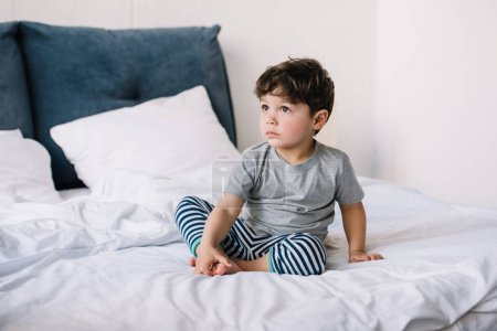 Photo for Cute kid with barefoot sitting on bed at home - Royalty Free Image