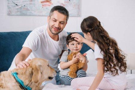 Photo pour Foyer sélectif de l'homme touchant golden retriever près des enfants à la maison - image libre de droit
