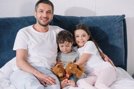 Photo pour Père gai s'asseyant sur le lit avec la fille heureuse et le fils triste d'enfant en bas âge - image libre de droit