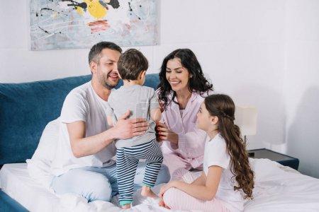 Photo pour Parents heureux regardant le fils d'enfant en bas âge près du descendant de sourire - image libre de droit