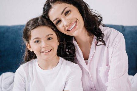 Foto de Happy mother looking at camera while smiling near daughter - Imagen libre de derechos