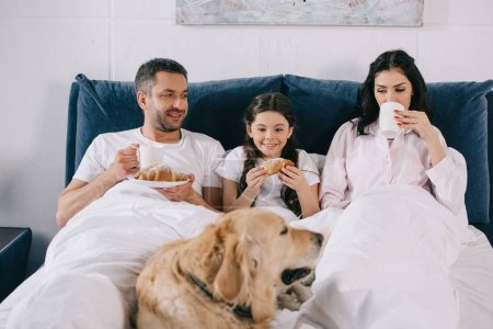 Photo for Selective focus of happy kid looking at dog lying on bed near parents with cups - Royalty Free Image