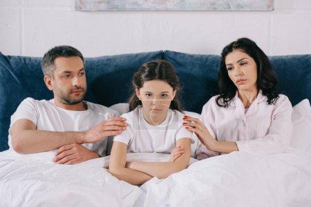 Photo pour Parents inquiets touchant un enfant bouleversé avec les bras croisés dans la chambre à coucher - image libre de droit