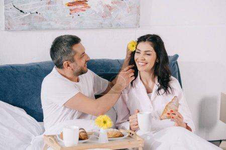 Photo pour Fleur gaie de fixation d'homme près de la femme heureuse avec la tasse et le croissant dans le lit - image libre de droit