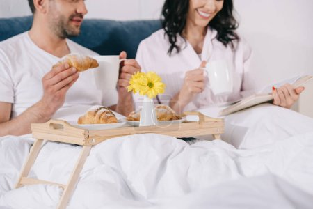 Photo for Cropped view of happy man holding croissant near woman reading in bed - Royalty Free Image