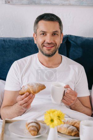 Photo for Cheerful man holding sweet croissant and cup of coffee in bed - Royalty Free Image